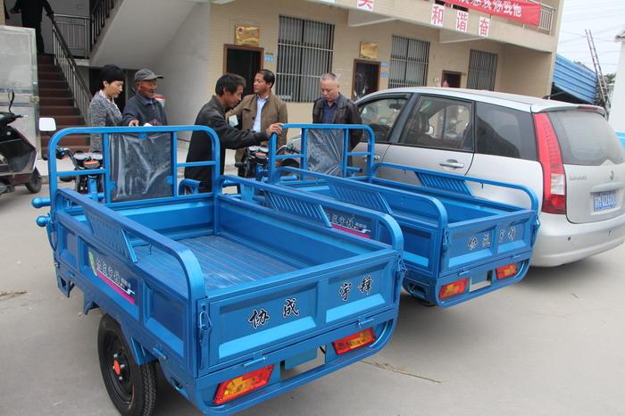 为困难群众送电动三轮车